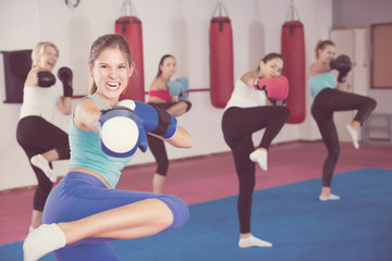 Group of young female are doing kick in gym