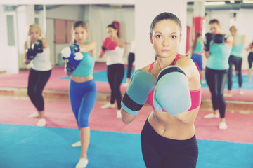 Portrait of sporty adult woman who is boxing