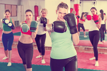Portrait of concentrated girl who is boxing with group in gym