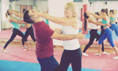 Mature woman is training self-defence moves in pair