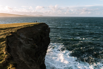 Woman standing near a cliff at Downpatrick Head on the atlantic ocean in Ireland during sunset
