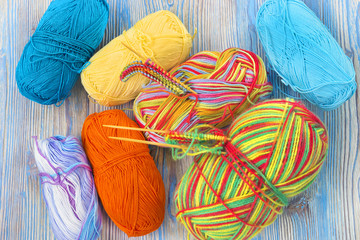 An overhead photo of the working place. Knitting needles and melange rainbow multicolor cotton yarn ball on the rustic wooden table.