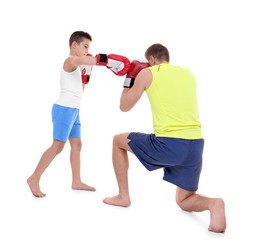 Cute little boy training with boxing coach, on white background