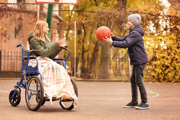 Little girl in wheelchair and boy playing with ball outdoors