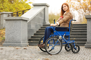 Young woman in wheelchair with cup of coffee outdoors