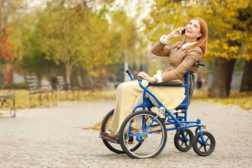 Young woman in wheelchair talking on phone outdoors