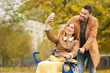 Young woman in wheelchair and her husband taking selfie outdoors