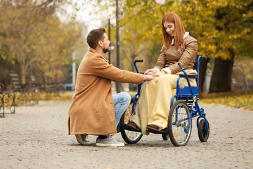 Young woman in wheelchair and her husband outdoors on autumn day