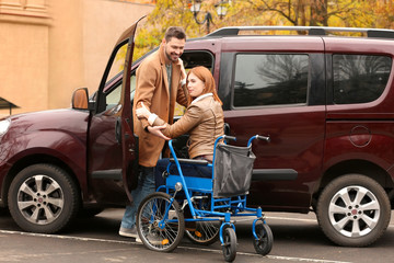Handsome man and woman in wheelchair near car