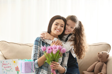 Young woman and her daughter with tulip bouquet indoors. Mother's day celebration