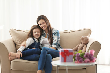 Young mother and her daughter hugging on sofa indoors