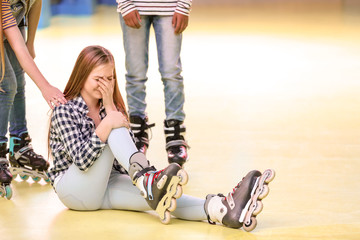 Teenage girl crying after falling down at roller skating rink