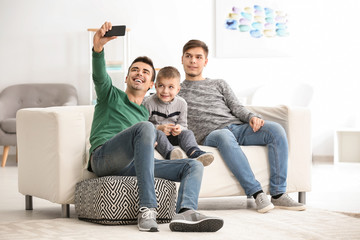 Male gay couple with adopted boy taking selfie at home