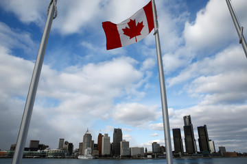 A Canadian flag flutters in front of the Detroit skyline, dominated by General Motors headquarters (R), is seen from Windsor, Onatario
