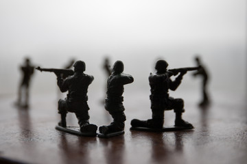 miniature toy soldiers and tank on board. Close up image of toy military at war.