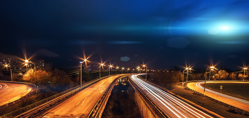 Bright blue light UFO ship fly above city and blurred road traffic at night