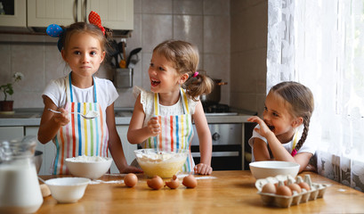 happy sisters children girls bake cookies, knead dough, play with flour and laugh  .