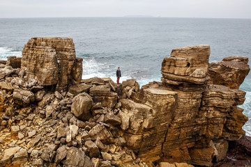 Man stands on a sea cliff, dark stormy sea on background. Young guy travel on the sea and stay on rocky shore under cloudy sky