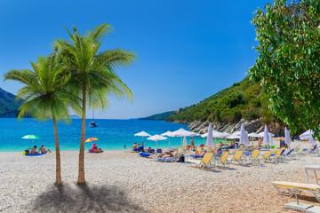 Beautiful summer holiday scene of Mikros Poros Gialos beach with people enjoying vacation in Lefkada island, Greece