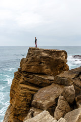 Man stands on a sea cliff, dark stormy sea on background. Young guy travel on the sea and stay on rocky shore under cloudy sky, vertical frame