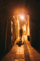 Illuminated cobbled street with light reflections on cobblestones in old historical city by night. Dark blurred silhouette of person goes in search of adventure in Old Jaffa in Tel-Aviv, Israel