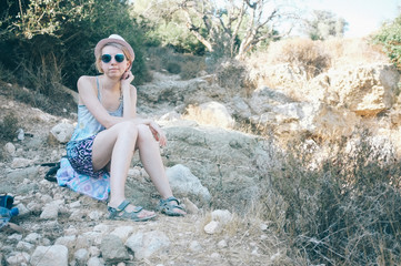 A girl sitting on the rocks with hat and sunglasses at the summer in Haifa, Israel
