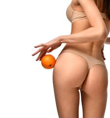 Young perfect woman in underwear hold orange showing absence of cellulite isolated