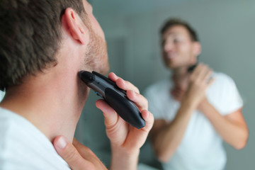 Man shaving beard using electric trimmer shaver. Male beauty grooming concept. Home lifestyle young person looking at bathroom mirror trimming hair on neck.