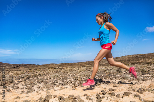 385582e85a83 Fit woman athlete trail running in outdoor desert. Side view of Asian girl  runner jogging