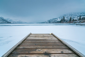 Winter landscape of wooden dock in foreground on frozen lake with snow covered mountains and fog in background
