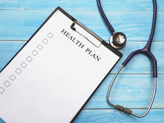 clipboard with white paper and stethoscope on wooden background.