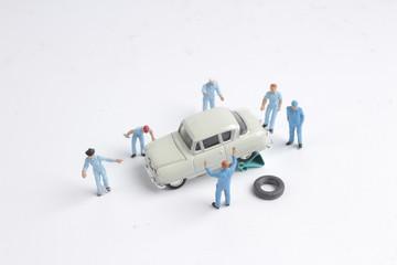 Mini tiny ofmechanics working on a car