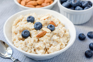 Oatmeal porridge bowl with almonds and blueberries. Closeup view