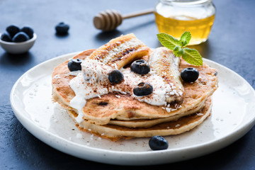 Oat pancakes with greek yogurt, roasted banana, blueberries and cinnamon on white plate