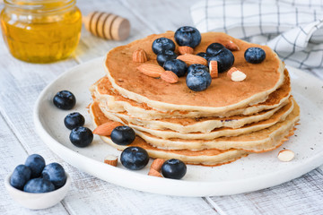 Gluten free oat pancakes with blueberries and almonds on white plate. Closeup view