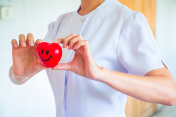 A nurse holding red heart toy. She is Left / right hand holding it.The photo shows the principle of caring and good health.
