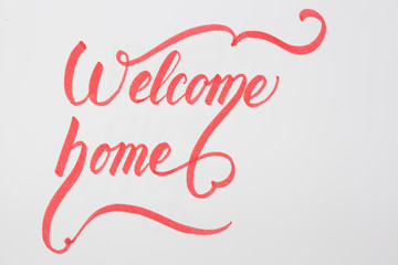 Welcome Home creative brush lettering on white background with copy space