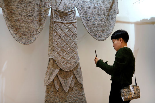 A visitor takes a picture of a creation of a Han-dynasty (202 BC-AD 220) costume by designer Wang Lei, which is made of old newspapers, in Beijing
