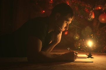 Person writes a letter to a Santa Claus under a Christmas tree branches at night. Student man is studying in Christmas holidays.