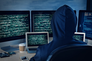 Man in hoodie hacking server at table