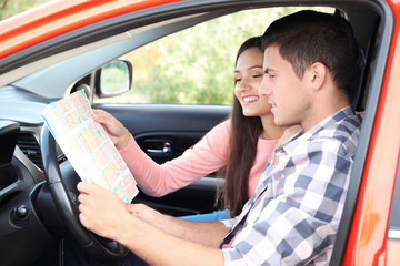 Young couple studying road map while sitting in car