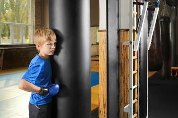 Cute little boy standing near punchbag in gym