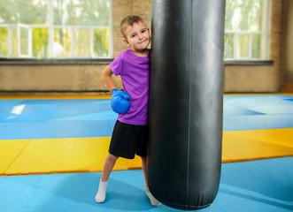 Cute little boy near punchbag in gym