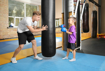 Little boy with trainer near punchbag in gym