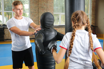 Little girl with trainer near punching dummy in gym