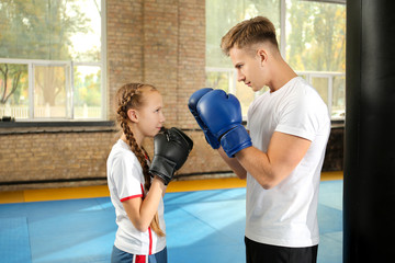 Little girl with trainer in boxing gloves indoors