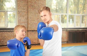 Little boy with trainer in boxing gloves indoors
