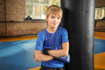 Cute little boy near punchbag in gym