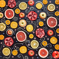 Colorful fruit pattern of fresh orange, apple, pomegranate, blueberry, persimmon, mandarin, cranberry and grapefruit slices on black background. Top view