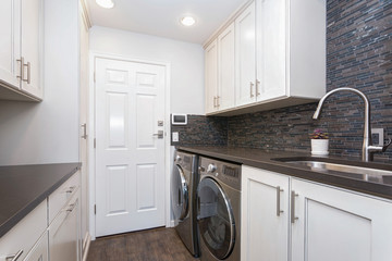White laundry room boasts white shaker cabinets